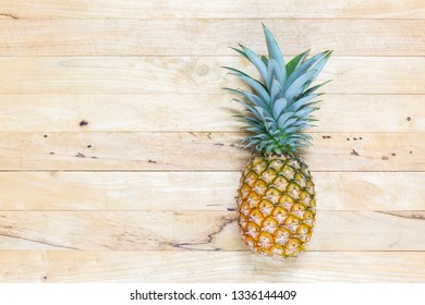 Single whole pineapple with green leaves on the wooden texture background. Top view.