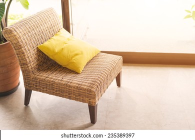 Single wickerwork chair and yellow cushion standing in front of a window alongside a potted houseplant
