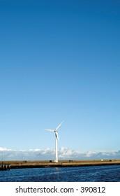 Single wind turbine against clear blue sky