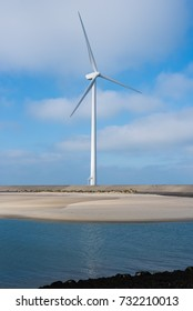 Single wind turbine at broad daylight. At the sea near the Delta Park, Zeeland, Netherlands. Windy weather and blue sky. Representing green energy