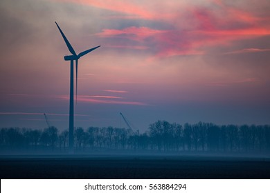 Single wind turbine in Dutch landscape during twilight with pink sky and trees on horizon