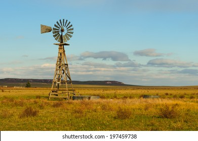 Single windmill stands on a farm at sunset.