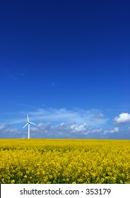 A single windturbine in a rapeseed field and a very blue sky