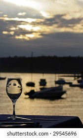 single wine glass at sunset