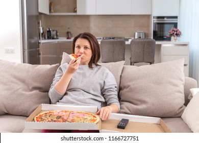 Single woman eating pizza and watching tv