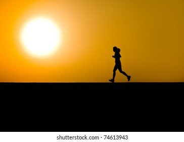 Single woman jogger in dramatic silhouette with large sun