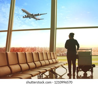 single woman sitting in airport terminal and passenger plane flying outdoor for traveling theme