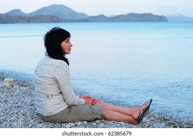 Single woman sitting on the empty beach relaxing