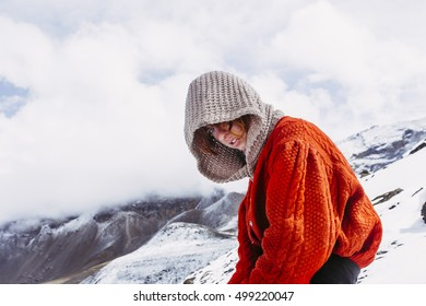 Single woman traveler sitting on the snow, with the hood on her head in Himalaya mountains, Nepal.
