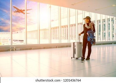 single woman and traveling luggage standing in airport terminal building