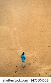 Single Woman Walks Lonesome On Abandoned Sand Beach