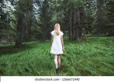 Single woman in white dress walks in dreamy green forest fairytale.