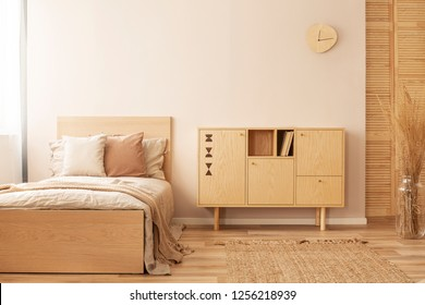 Single wooden bed with beige bedding and blanket next to stylish wooden cabinet in elegant bedroom