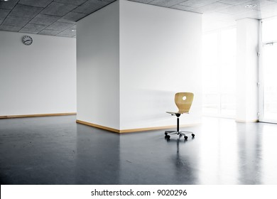 a single wooden chair in a bright empty room with a wall clock and sunlight and sunbeams shining from outside