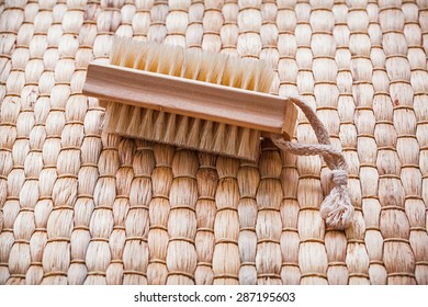 Single wooden scrubbing bath brush on wicker mat healthcare concept