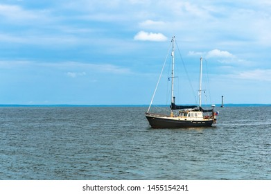 single yacht with lowered sails, black and white yacht on the water, Baltic sea ,Kaliningrad region, Russia, September 8, 2018