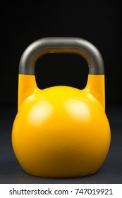 Single yellow competition kettlebell on a weight training gym floor. Potential text / writing space on and above kettlebell. Yellow competition kettlebells weigh 16kg.