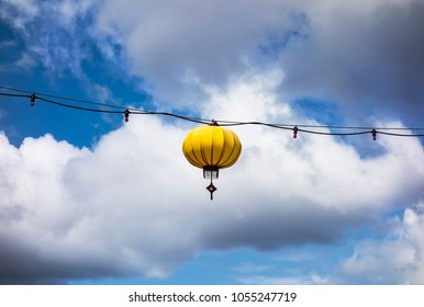 A single yellow lantern hangs from a wire that is stretched across a street in the Chinatown area of Victoria, British Columbia.