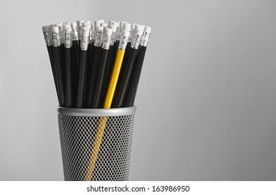 Single yellow pencil in pot of black pencils.