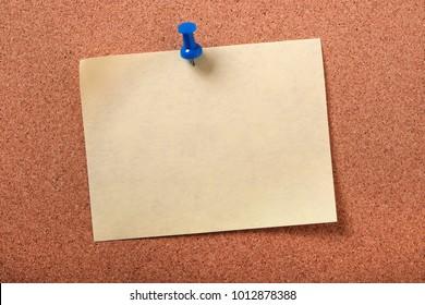 Single yellow sticky post note pinned pushpin cork board