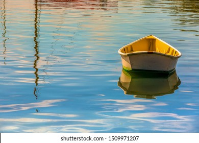 Single yellow and white painted wooden row boat or dingy floating at anchor on vivid blue ocean water with the reflection of a sailboat mast