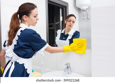 Single young adult female hotel maid using yellow cloth and rubber gloves to tidy up low section of mirror in bright bathroom