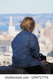 Single young blond woman sitting and looking at the city of San Francisco, with the Transamerica Pyramid tower in background