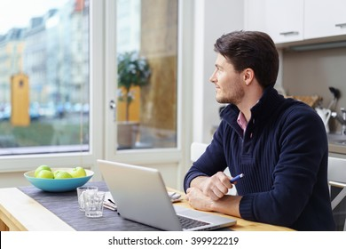 Single young man wearing blue collar sweater seated with laptop on table in kitchen looking out window