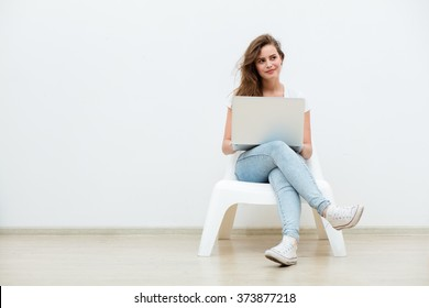 single young woman sitting on a white chair with laptop in an empty room, thinking on something