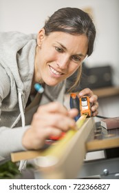 Single young woman standing by workbench at home