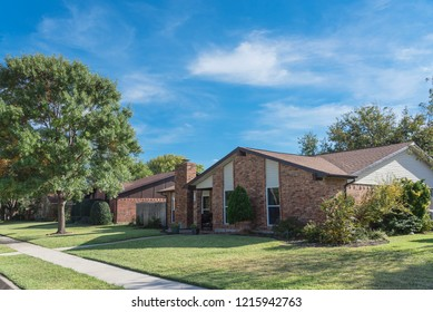 Single-detached dwelling home in suburban Dallas-Fort Worth with attached garage. Colorful autumn fall foliage in North America.