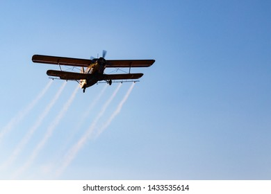 Single-engine biplane spraying mosquitocide chemical over the city