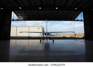 Single-engine, high wing aircraft parked in an aircraft hangar with the door open.  Shiny floor reflecting the sky and other buildings.