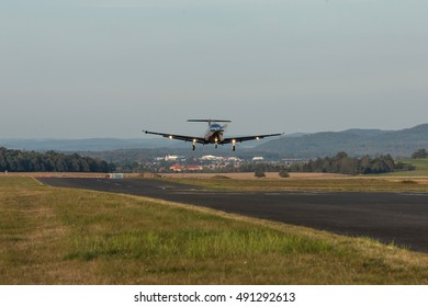 Single-engine turboprop aircraft departing from a small airport.