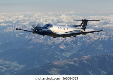 Single-engine turboprop aircraft flying over the Alps in Austria.