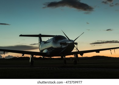 Single-engined business airplane on runway at twilight time.