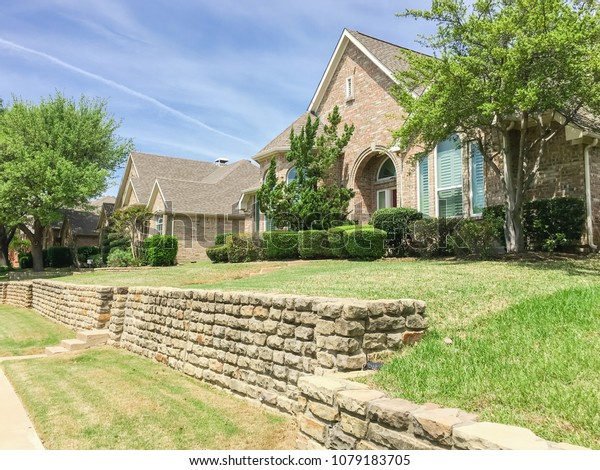 Single-family home with brick and stone elevation above street level in Irving, Texas, USA. Lush landscaping neighborhood with concrete walking biking trail. Terrain house on elevated lots