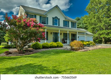 Single-family home with large lawn and landscaping under a blue sky.