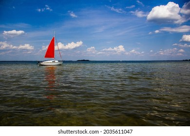 Single-masted sailboat with red sail
