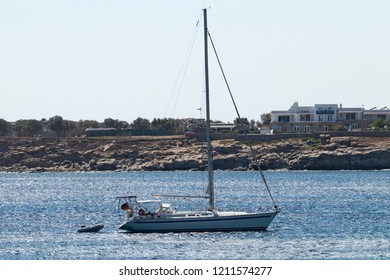 SIngle-masted sailing yacht anchored off the shores of Mykonos, Greece.