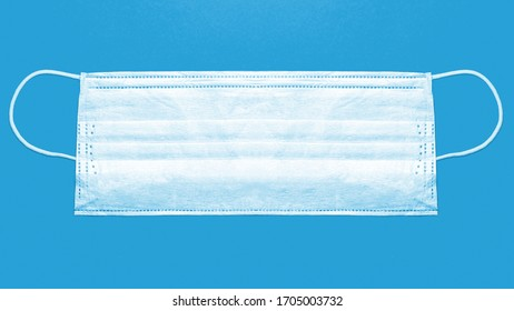Single-use medical face mask on blue background