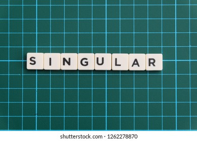 Singular word made of square letter block on green square mat background.
