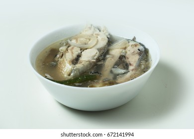 Sinigang na bangus or milkfish in sour broth is a Filipino Traditional Dish. The sour taste of tamarind gives the distinctive taste of the broth. Isolated on White perspective shot.