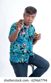 The sinior man holding the glass of whiskey and cigarette, sitting on a chair and used hands pointing straight forward, on white background