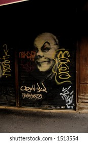 Sinister clown face painted on the security grill of a bistro in Paris called, appropriately, the Clown Bar.