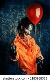 Sinister clown man stained in blood holding a balloon. Male zombie clown. Halloween. Horror.