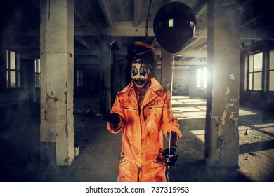 Sinister clown man stained in blood is standing in an abandoned house with a balloon. Male zombie clown. Halloween. Horror.
