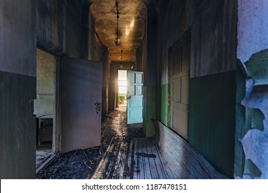 Sinister and creepy Corridor of abandoned hospital after fire. Ceiling in black soot.