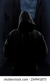 A sinister figure in a dark alley, face covered by a hood.