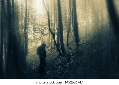 A sinister figure, with glowing eyes, looking at the camera, silhouetted on a path in a forest. With a spooky, vintage edit.